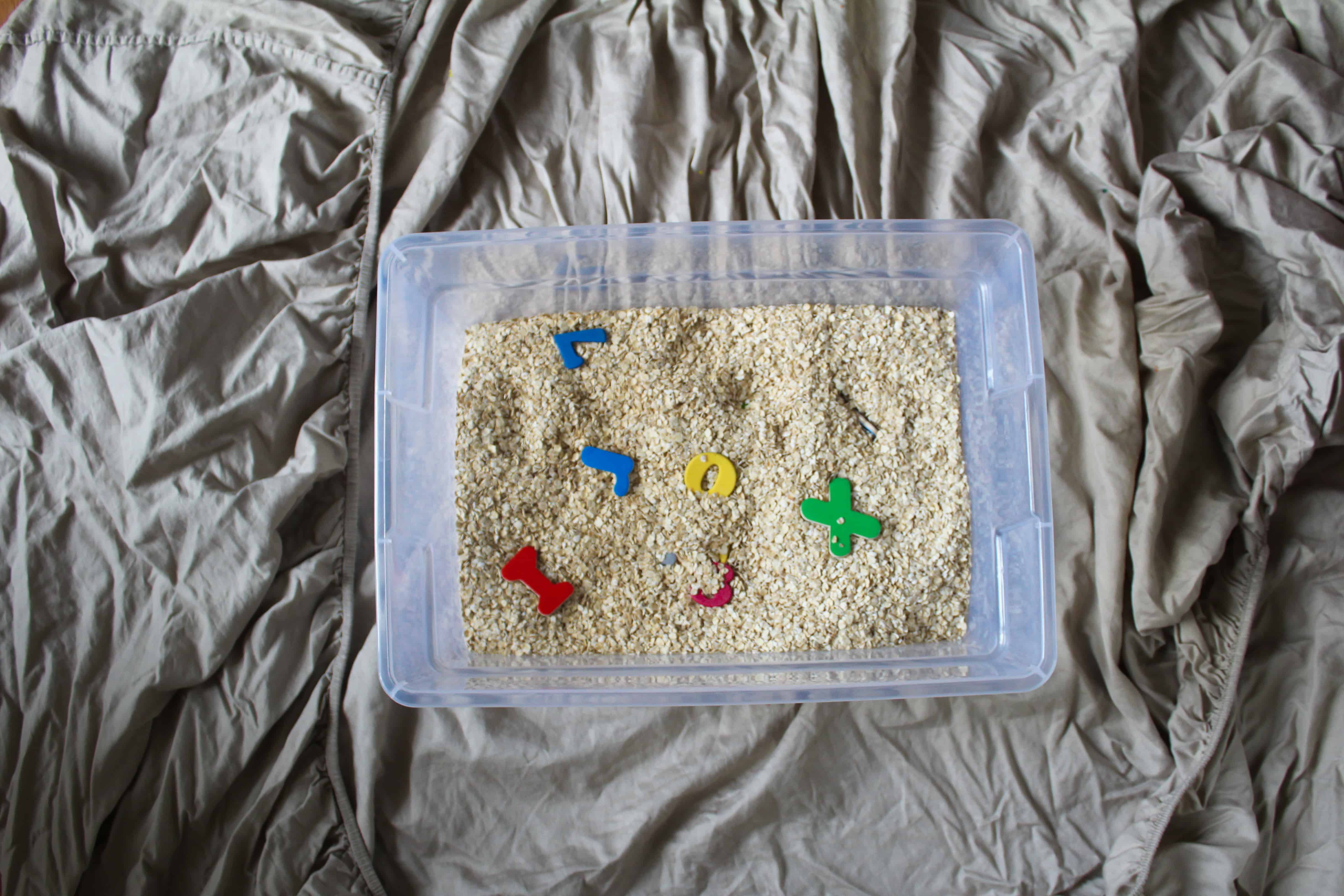 Fun toddler friendly sensory activities. This sensory box has oatmeal and incorporated wooden alphabet letters in order to explore early letter recognition.
