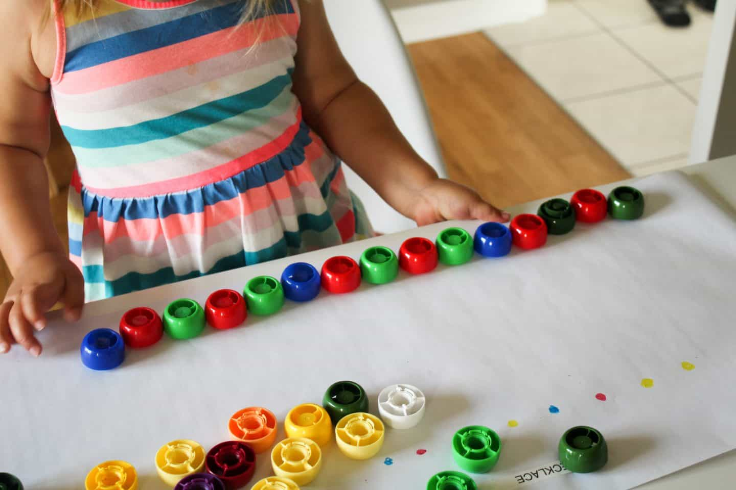 A fun pattern activity for preschoolers using baby food pouch caps and making a necklace