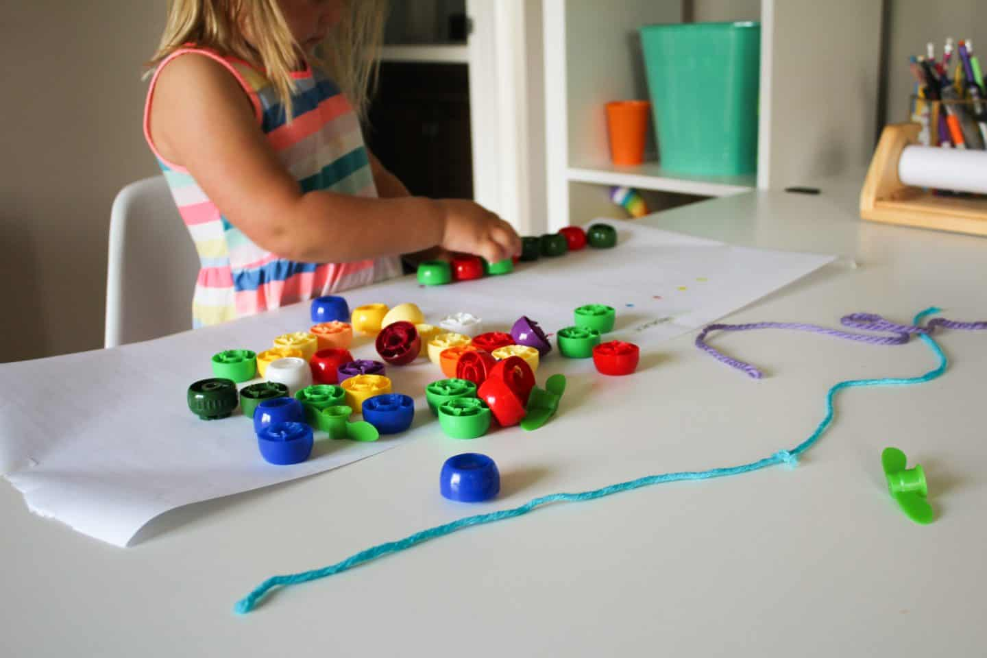 Pouch cap craft activity for toddlers and preschoolers. A fun way to reuse pouch caps for a necklace threading activity