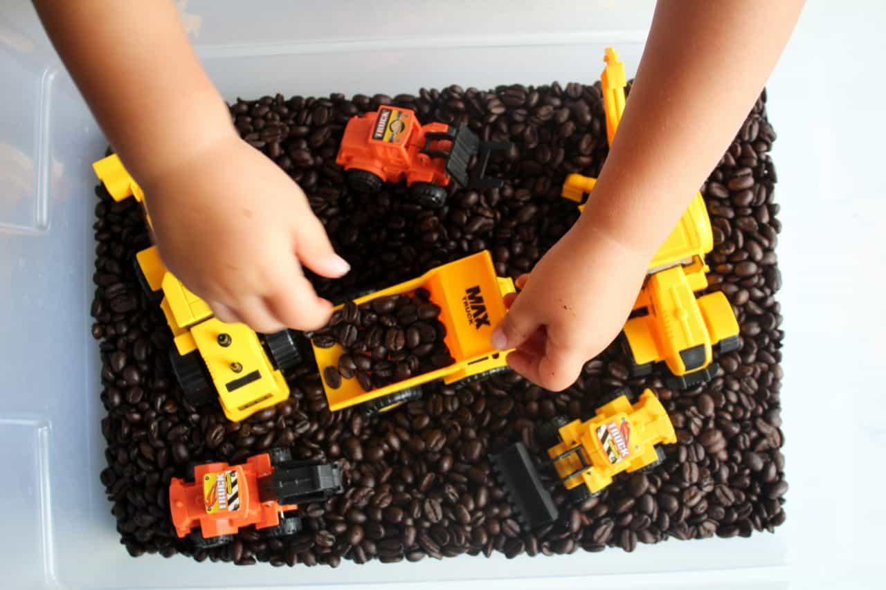 Coffee bean sensory bin, using coffee beans as the base of the sensory bin and adding in construction trucks and equipment #sensorybin #sensorybox #sensoryplayfortoddlers #sensoryideas