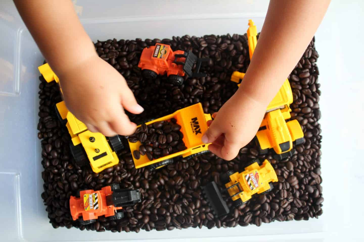 Coffee bean sensory bin, using coffee beans as the base of the sensory bin and adding in construction trucks and equipment #sensorybin #sensorybox #sensoryplayfortoddlers #sensoryideas